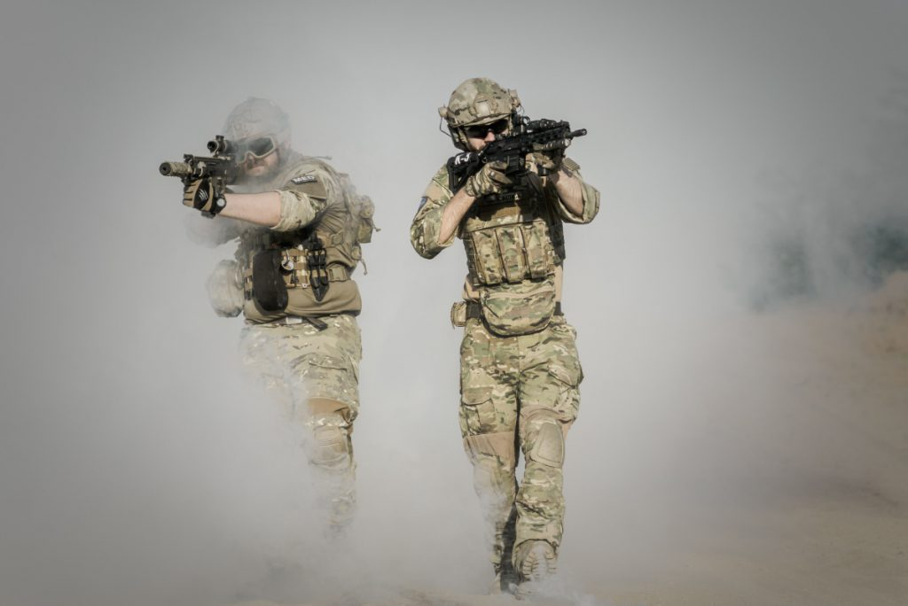 Two soldiers walking through smoke aiming their guns. Power tactics.