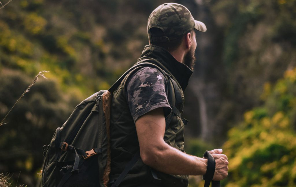 man hiking with a walking stick wearing survivalist gear while looking at the landscape.