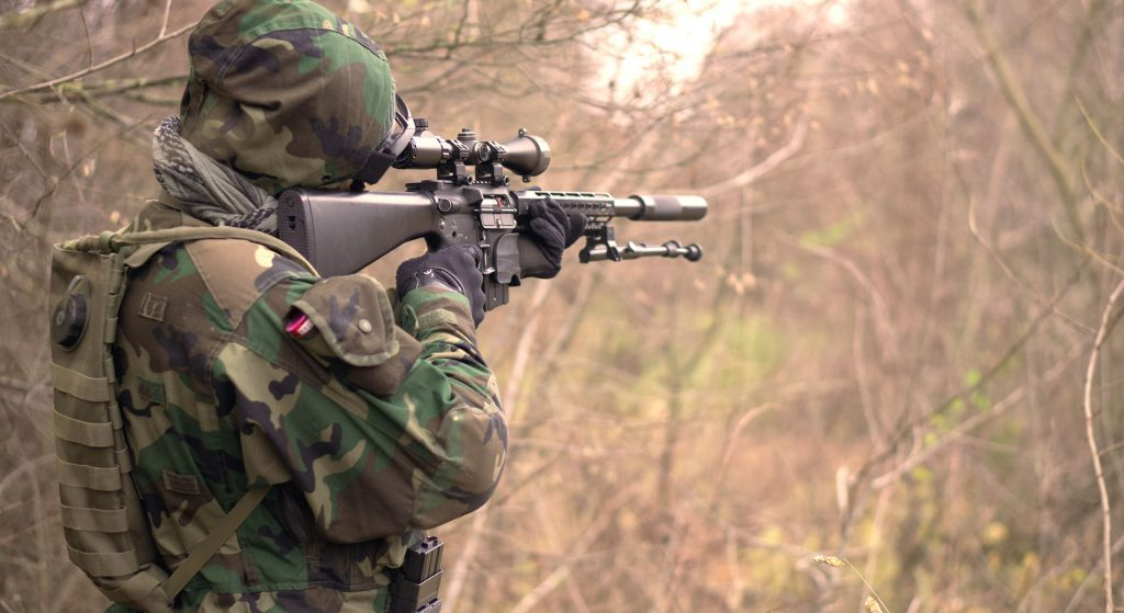 man wearing tactical gear and body armor pointing a rifle in the distance through brush. Tactical body armor failures