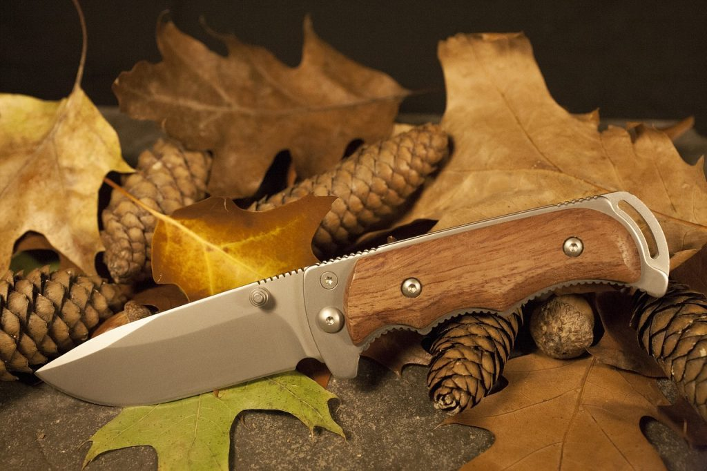 A brown tactical folding knife sitting in front of old leaves and pine cones.