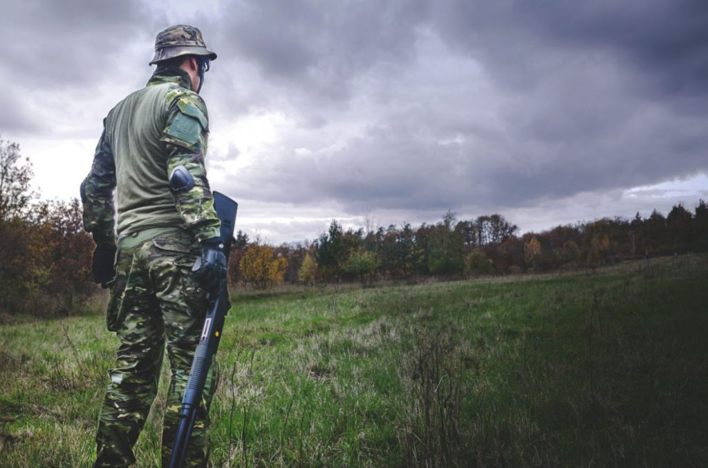 man standing in a grassy field under stormy weather wearing camo holding a gun. Psychology of body armor