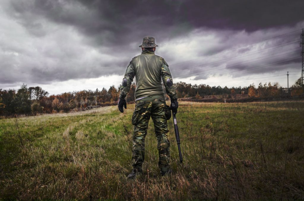 man standing with back to the camera in a field with stormy weather