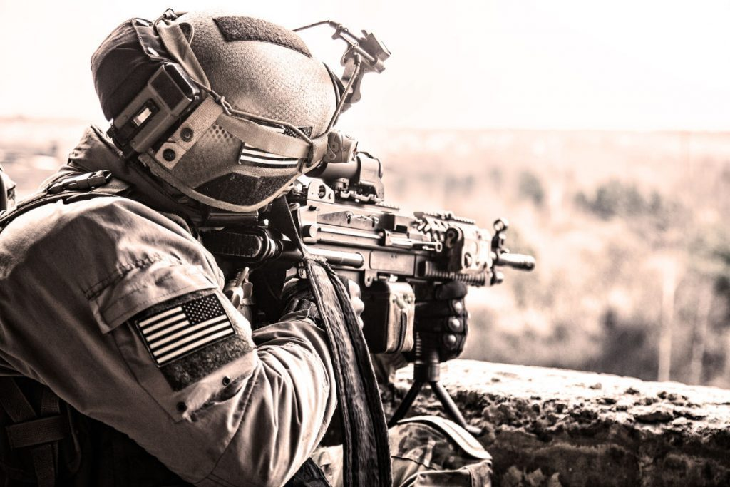 man wearing tactical survival gear pointing gun out into the distance
