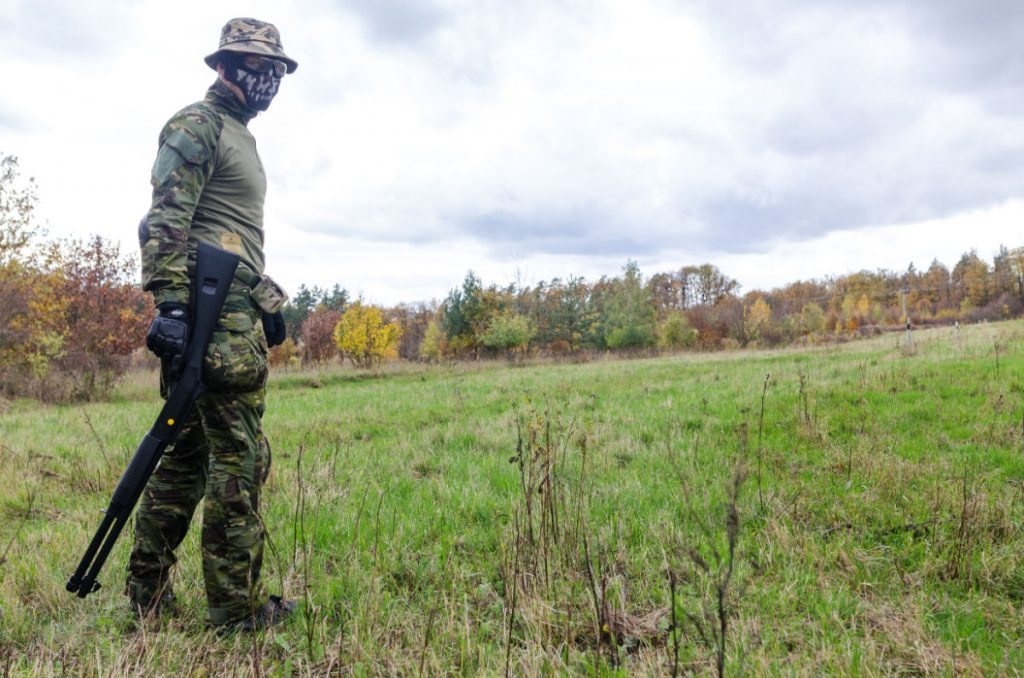 man wearing scary face mask standing in a green field