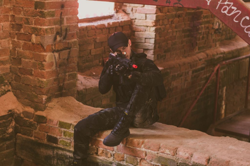 Man dressed in black tactical carrier armor sitting on a brick wall of an abondoned building