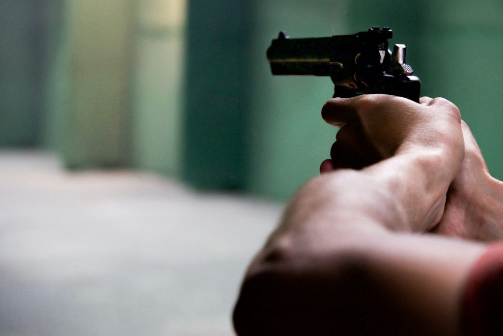man with black revolver in shooting range pointing gun off screen.