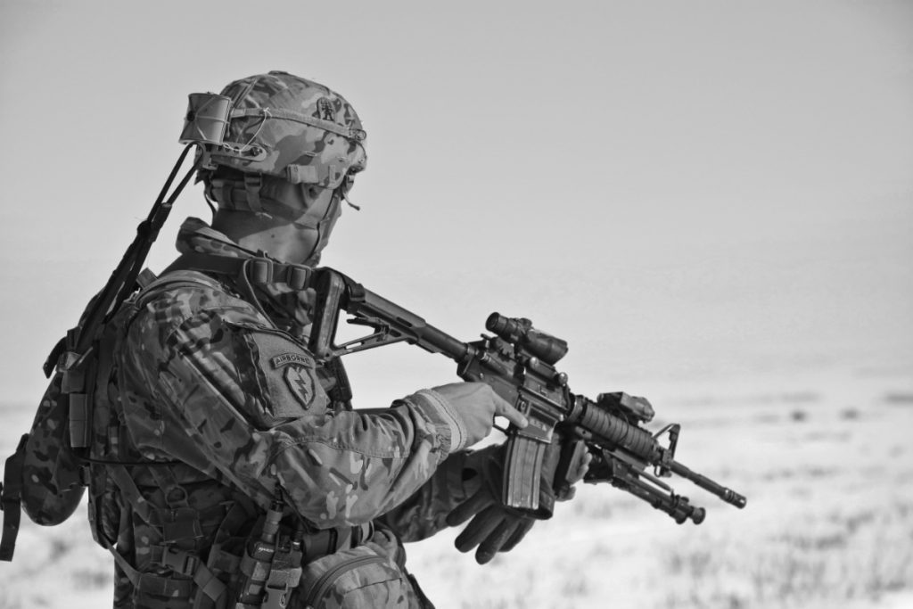 miltiary man in black and white holding rifle looking off into the distance.
