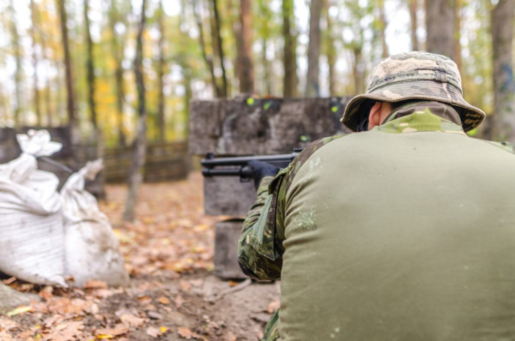 man in green pointing black shotgun at ar500 target off-screen in a forest.