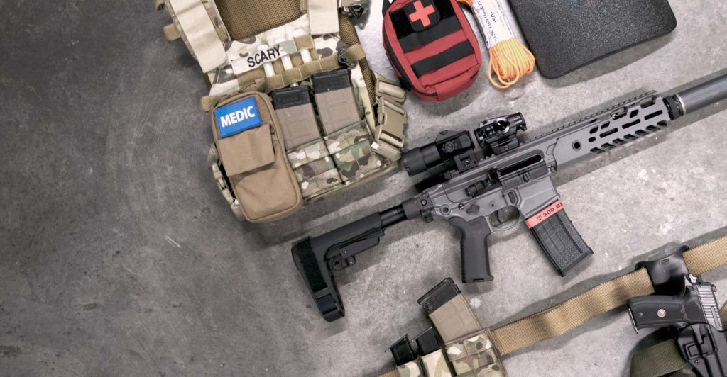 Tactical survival gear items. A backpack, medpack, gun, and holster all lying on a concrete floor